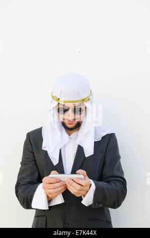 Arab man touching smartphone in outdoors white wall - Stock Photo