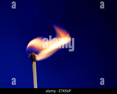 Macro shot of a flaming matchstick on blue - Stock Photo