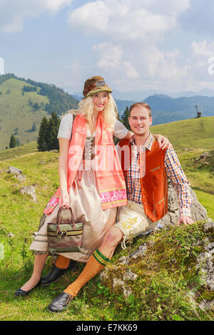 Lovers pants in fashionable traditional Bavarian Dirndl and leather with hat - Stock Photo