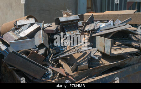 A skip full of rusting scrap steel and other metal sits waiting for collection and recycling. - Stock Photo