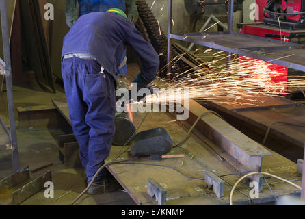 An African artisan boiler maker works with an angle grinder whilst training an apprentice. - Stock Photo