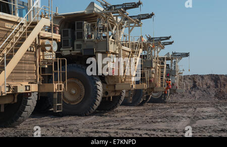 Massive Hitatchi mining trucks park up in line during shift change at an open cast African copper mine. - Stock Photo