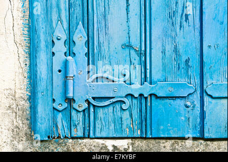 Decorative hinge on an old blue wooden window shutter - Stock Photo