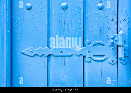 Decorative hinge on a blue painted wooden door with rain drops - Stock Photo