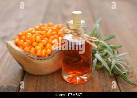 Sea-buckthorn oil and berries in bowl on a wooden background - Stock Photo