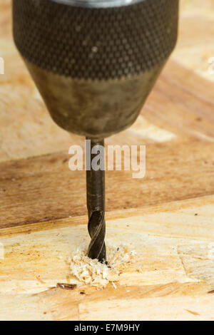 Close-up of Auger bit drilling wood - focus on wood - Stock Photo