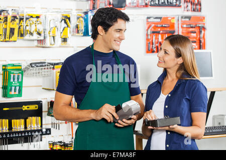 Woman Looking At Worker Swiping Credit Card - Stock Photo
