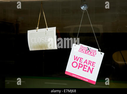 Signs on shop door - open and closed - england uk - Stock Photo