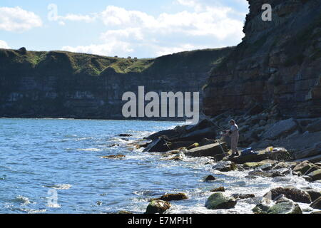 Man fishing on rocks in cove - Stock Photo