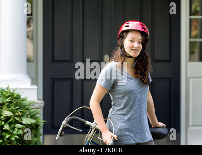 Image of teenage girl, looking forward with helmet on, while resting against her bicycle with home in background - Stock Photo