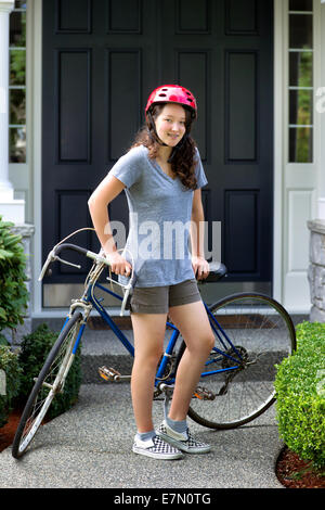 Vertical image of teenage girl, looking forward, while resting against her bicycle with home in background - Stock Photo
