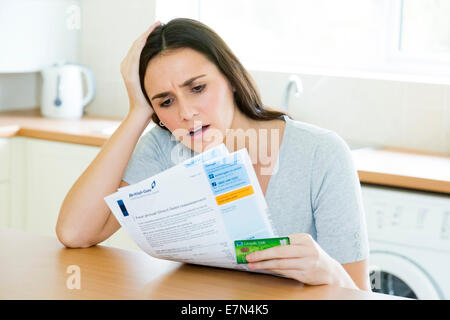woman worried about her gas utility bill / statement - Stock Photo