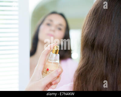 young woman spraying Pret-A-Porter perfume - Stock Photo