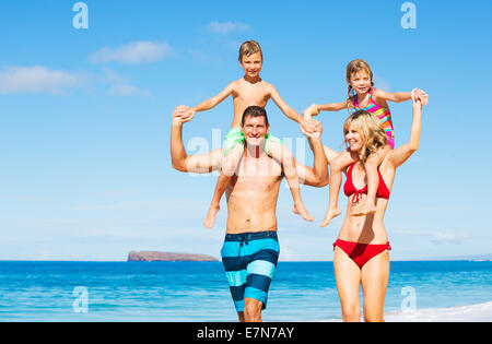 Happy Family of Four Having Fun on the Beach - Stock Photo