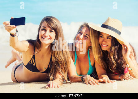 Girls having fun at the beach taking self portrait with smart phone. Summer Fun Lifestyle. - Stock Photo