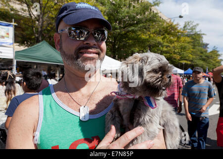 Man holding up a Pekingese dog in arms - USA - Stock Photo