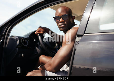 Portrait of muscular young man in car. African male model wearing sunglasses sitting on driver seat looking at camera. - Stock Photo