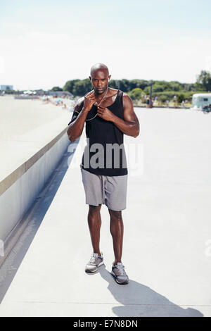 Full length portrait of fit young man outside listening to music on earphones. Muscular young male model. - Stock Photo