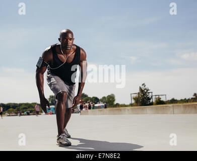 Fit young man on his mark to start running. Determined athlete outdoors. Muscular African male model ready for his - Stock Photo