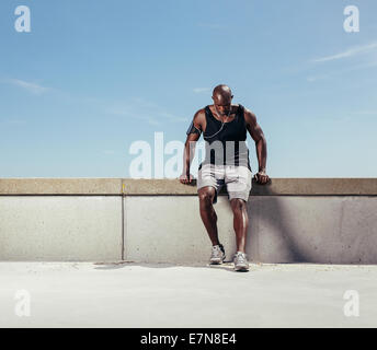 Muscular young man taking breath after his run. African male athlete outdoors with copy space. Male runner relaxing - Stock Photo