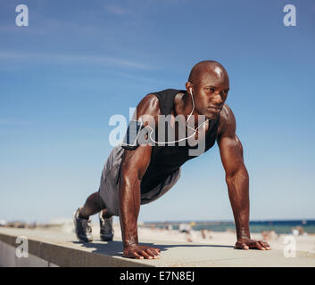 Muscular man doing push ups against blue sky. Strong male athlete working out outdoors. - Stock Photo