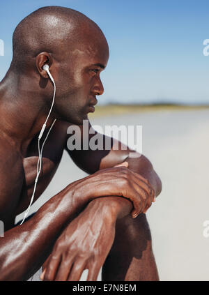 Close-up image of African man wearing earphones sitting alone. Muscular young man looking away in though - Stock Photo