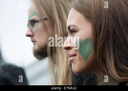Oslo, Norway. 21st Sep, 2014. A woman and mand with green hearts painted on their faces join thousands marching - Stock Photo