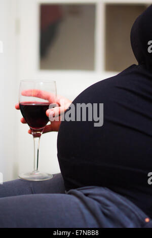 Pregnant woman holding a glass of wine - Stock Photo