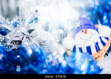 Christmas decoration with smiling snowman. Abstract blue holiday decorations: baubles, stars, tinsel and garland. - Stock Photo