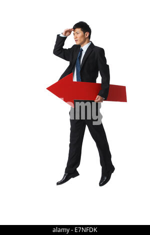 Business man holding a red arrow - Stock Photo