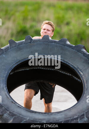 Athlete Lifting Large Tractor Tire - Stock Photo