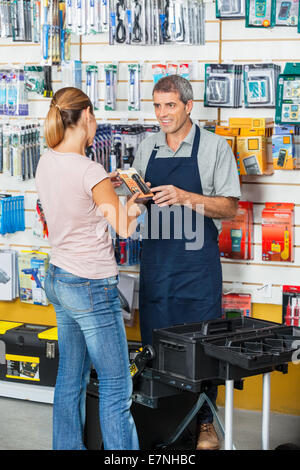 Salesman Showing Flashlight To Customer In Hardware Store - Stock Photo