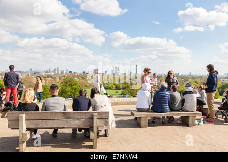 London viewpoint. People sitting on benches in the Spring sunshine viewing the distant city skyline from Primrose - Stock Photo