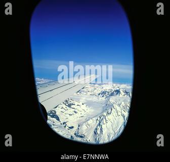 Aerial view of snowy Alps mountains through airplane window Switzerland Europe - Stock Photo