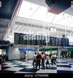 Travellers and departures and arrivals boards Franz-Joseph Strauss airport Munich Bavaria Germany Europe - Stock Photo