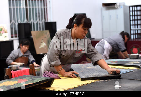 Pingyao, China's Shanxi Province. 20th Sep, 2014. Craftswomen refine pieces of lacquerware in Pingyao, north China's - Stock Photo