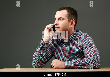 Portrait of businessman sitting at the table and talking on the phone - Stock Photo