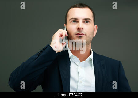 Portrait of a thoughtful businessman talking on the phone - Stock Photo