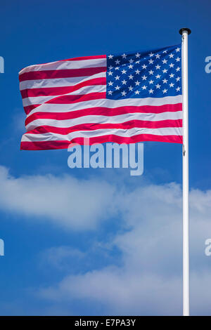 Stars and Stripes / North American national flag of the USA on flagpole flying in the wind against cloudy sky - Stock Photo