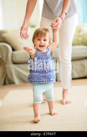 Mother assisting baby daughter (18-23 months) with her first steps - Stock Photo