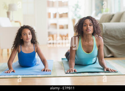 Mother and daughter (8-9) exercising in living room - Stock Photo