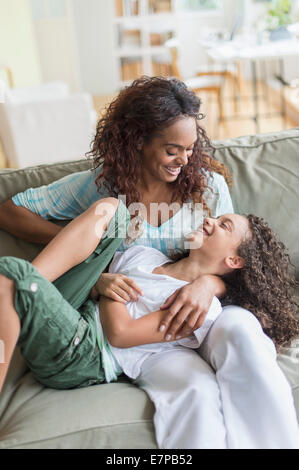 Mother tickling daughter (8-9) on sofa - Stock Photo