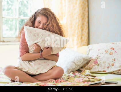 Portrait of woman embracing pillow - Stock Photo