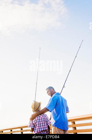 Father and son (10-11) fishing - Stock Photo
