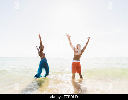 Mature couple standing in sea with arms raised - Stock Photo