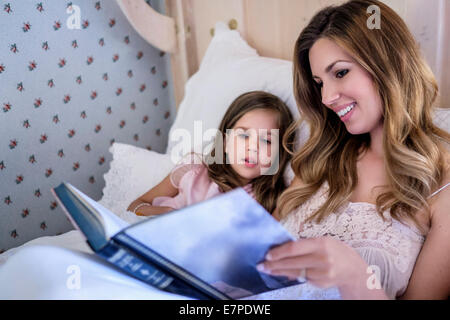 Mother reading bedtime story to her daughter (4-5) - Stock Photo