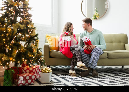 Young couple with Christmas stockings on sofa - Stock Photo