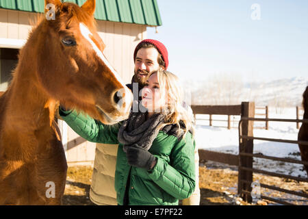 USA, Utah, Salt Lake City, Young couple stroking horse - Stock Photo