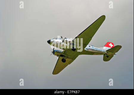 A Douglas DC-3 (Dakota) aircraft, of Swissair, coming in to land against a grey sky - Stock Photo