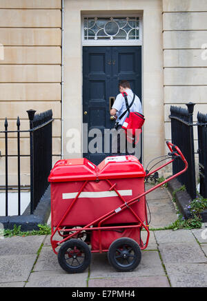 Postman delivering letter and mail through a Bristol house front door with the aid of a red mail cart - Stock Photo